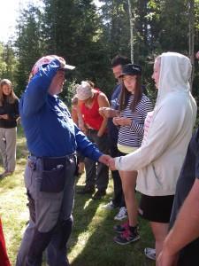 Lägerchefen delar ut deltagarmärke till Issa och gör scouthälsning